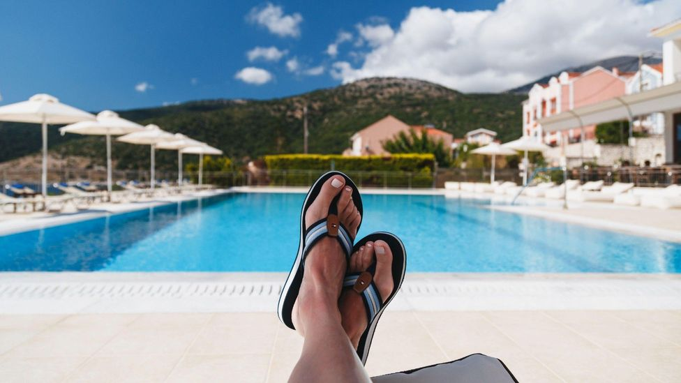 Stock image of a woman's feet by a pool in Greece on 14 July 2019