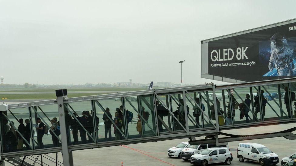 Passengers can spend several minutes queueing in crowded, poorly ventilated walkways as they board the plane