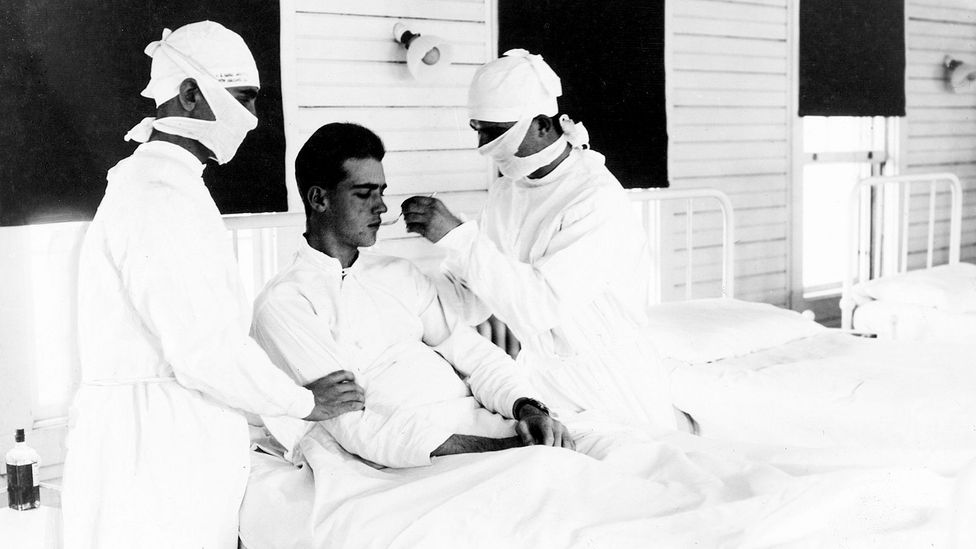 Doctors treat a flu patient in New Orleans in 1918; some five million pandemic survivors have experienced extreme long-term exhaustion (Credit: Getty Images)