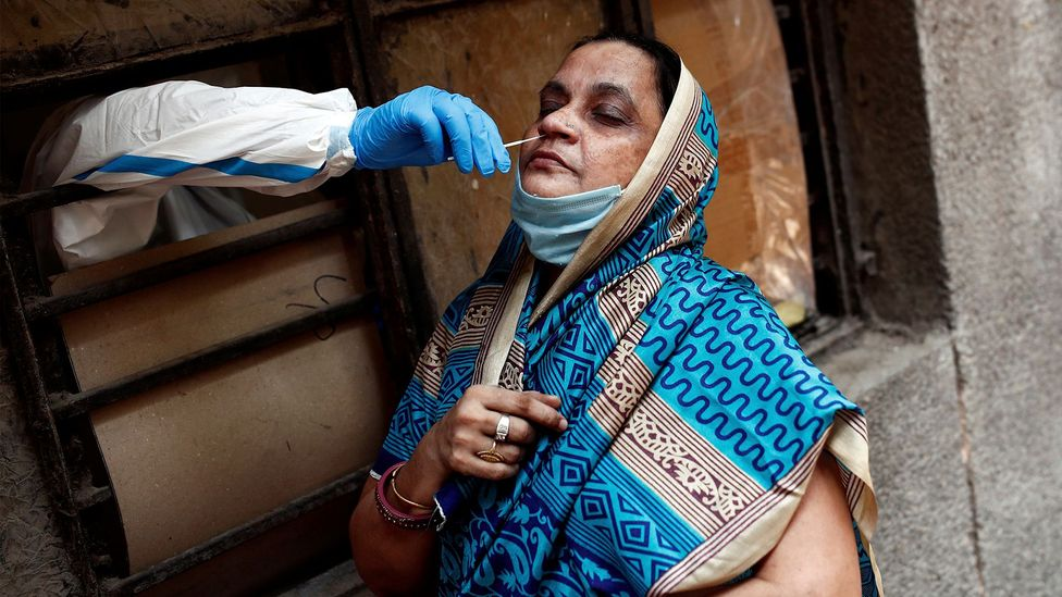 A medical worker takes a sample to test the Covid-19 in New Delhi; many people with the virus are never tested (Credit: Reuters)