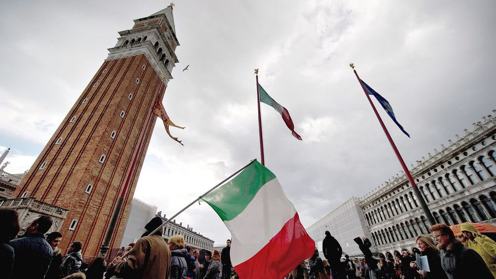 Flags fly in Venice during a one-off holiday in Italy in 2011. It was found to have a positive economic impact – unlike proposed holidays in other countries (Credit: Getty Images)