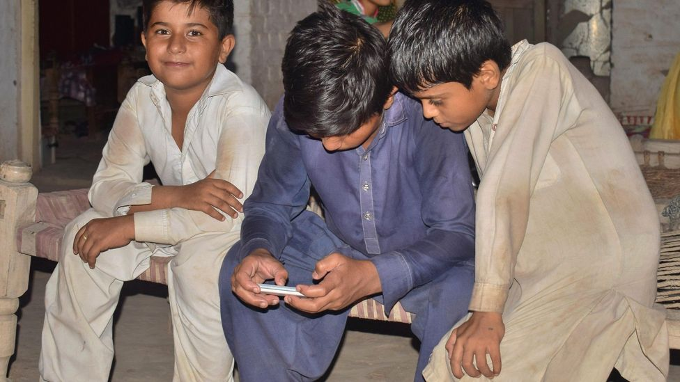 Pakistani boys looking at a smartphone