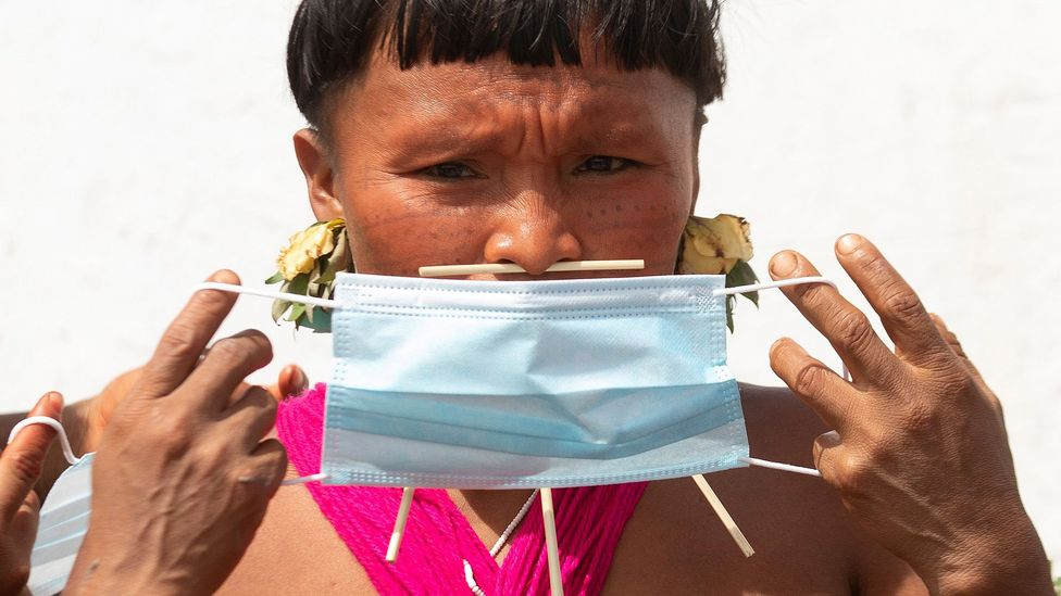 A member of the Yanomami people holds a face mask during a health brigade by the Brazilian Army in Alto Alegre municipality (Credit: EPA)