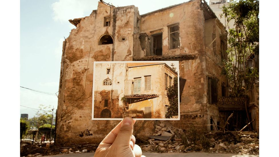 A new series of photographs shows Khoury and Cardozo holding up their postcards in front of the structures shattered by the explosion (Credit: Joseph M Khoury)