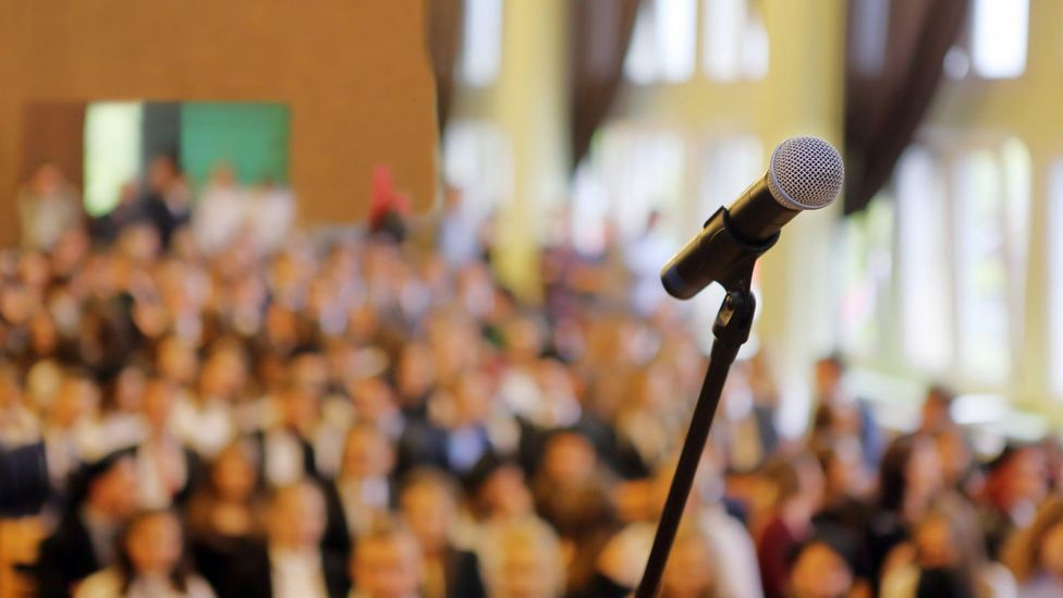 File image of a microphone in front of a blurred conference audience
