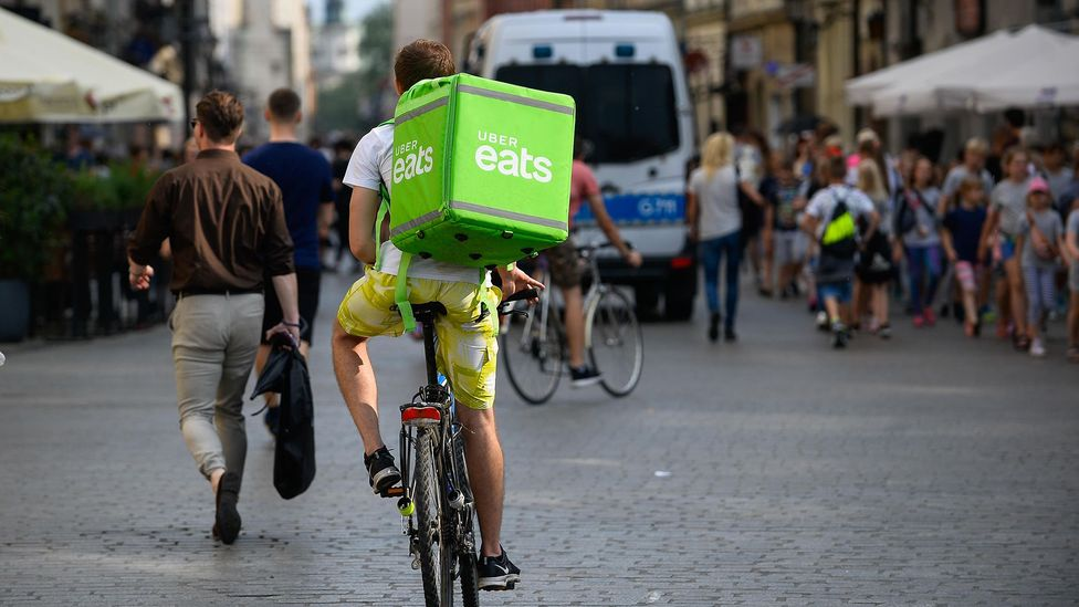 An Uber Eats courier in Krakow, Poland. Gig economy giants like Uber rely heavily on algorithms to determine how to allocate work, reward workers, and more (Credit: Alamy)
