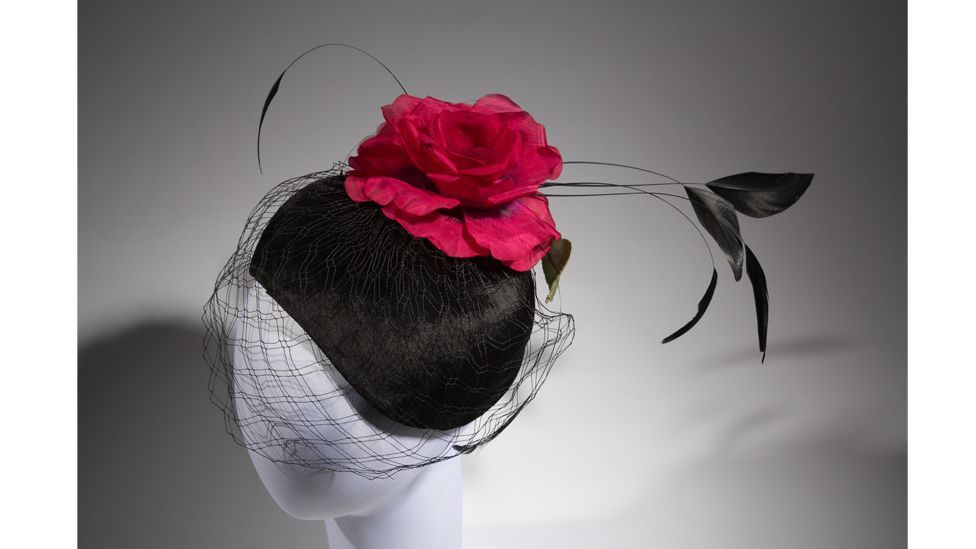 Created in the 1950s by Elsa Schiaparelli, a hat complete with red-and-green silk organza rose (Credit: Museum at FIT)