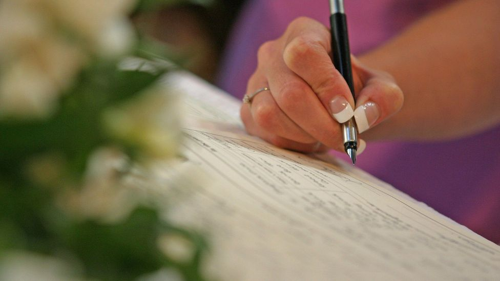 Woman signing the marriage registry - file image