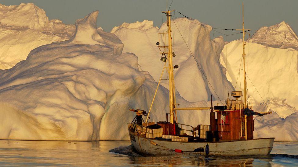 A Greenlandic boat cruises past an iceberg (Credit: BBC)