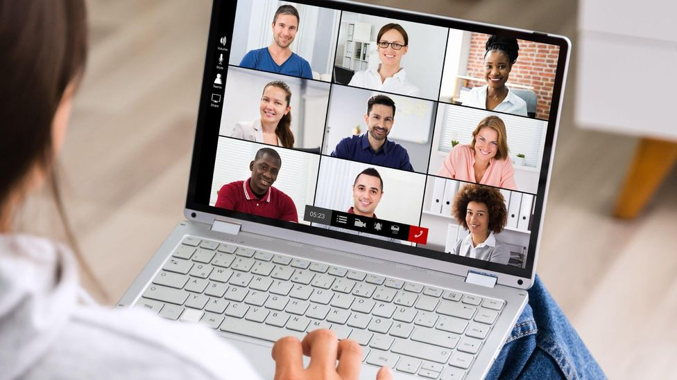 File image of a worker looking at faces of several colleagues on screen