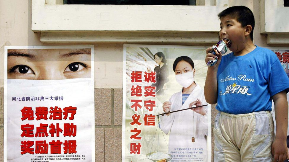 In front of posters about the Sars epidemic, a boy eats ice cream, which we collectively spend more on than preventing extinction through our technology (Credit: Getty Images)
