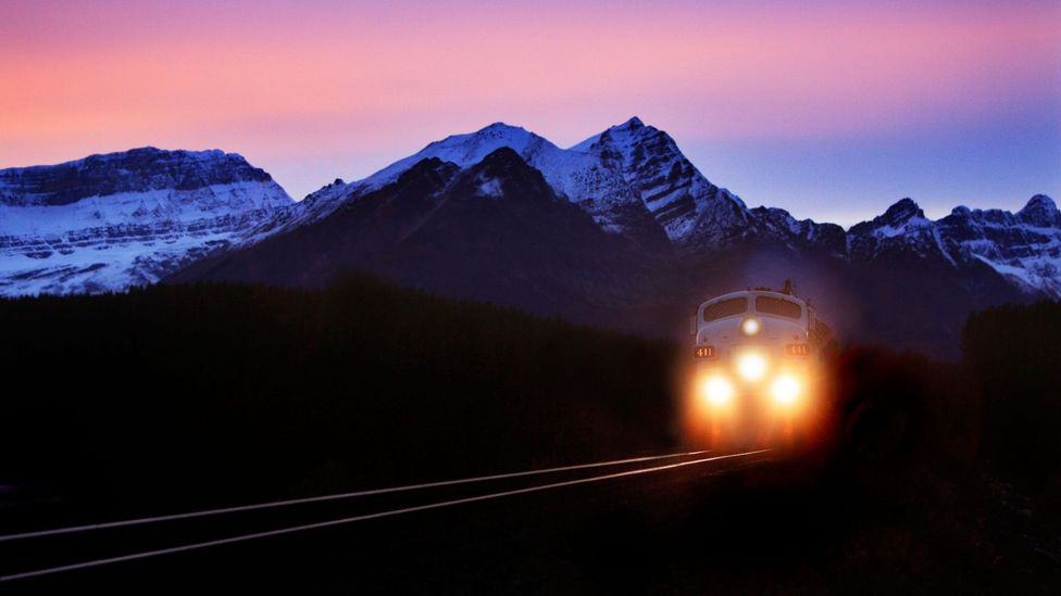 File image of a train travelling past mountains are dawn