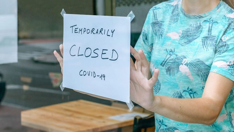 File image of woman placing a 'Closed' sign on a cafe