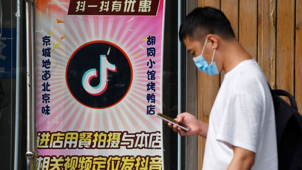 A man walks past a Beijing restaurant which offers a discount to anyone who posts videos on TikTok (Credit: Greg Baker/Getty Images)