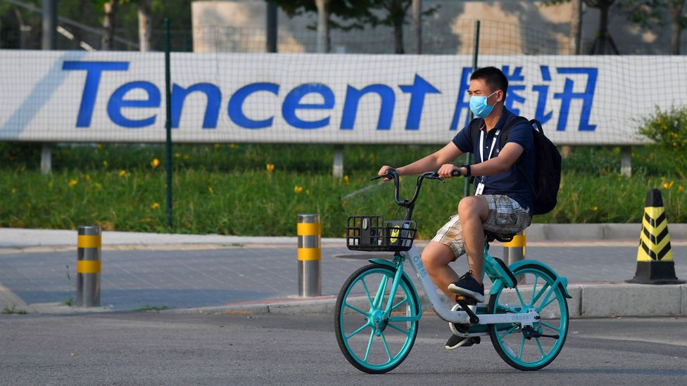 A man cycles past Tencent, the parent company of Chinese social media giant WeChat (Credit: Greg Baker/Getty Images)
