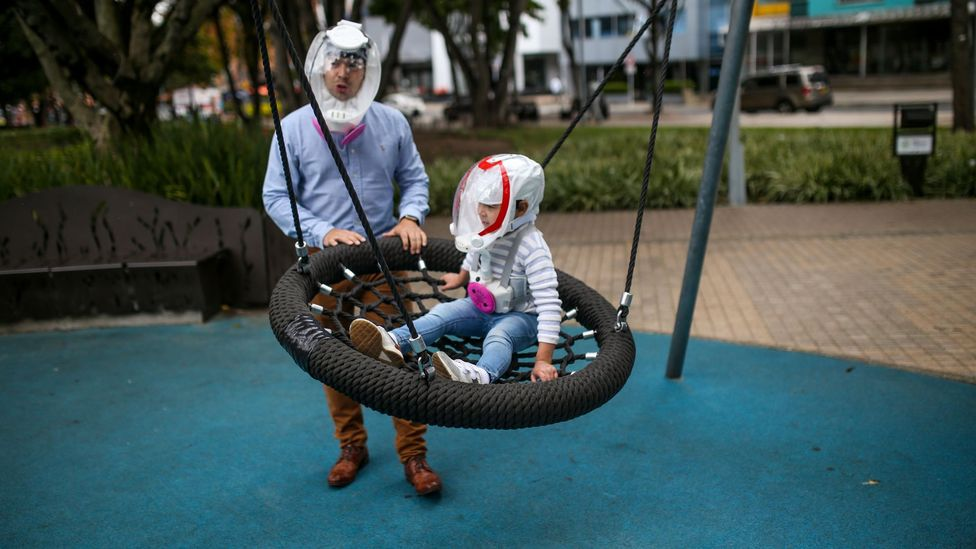 Man and child with anti-Covid helmets (Credit: Anadolu Agency/Getty Images)