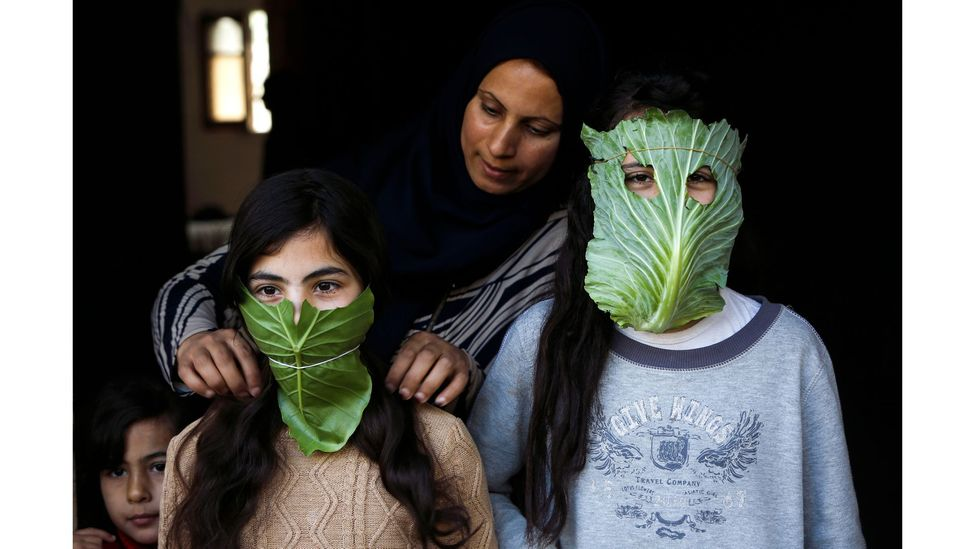 A Palestinian mother entertains her children with makeshift masks made of cabbage as she cooks in Beit Lahia in April 2020 (Credit: Mohammed Abed/AFP via Getty Images)