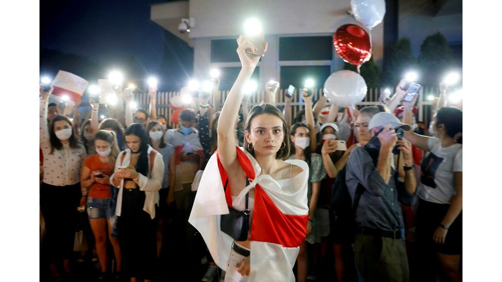 A demonstrator holds up her phone during a march after the disputed presidential election in Belarus, August 2020 (Credit: Kacper Pempel/Reuters)