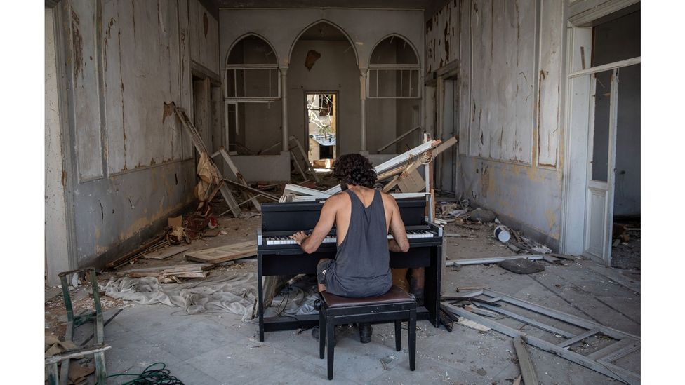 Raymond Essayan plays a piano in a destroyed building on 14 August, 2020 after the port explosion in Beirut, Lebanon (Credit: Chris McGrath/Getty Images)