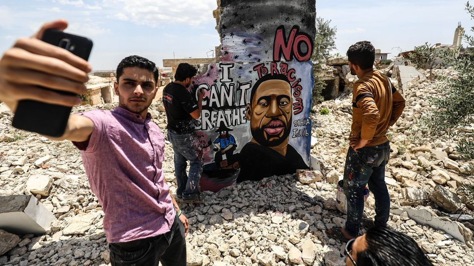 A friend of the muralist Aziz Asmar takes a selfie as the artist works on his Floyd memorial in Idlib, Syria (Credit: Izzeddin Idilbi/ Getty Images)