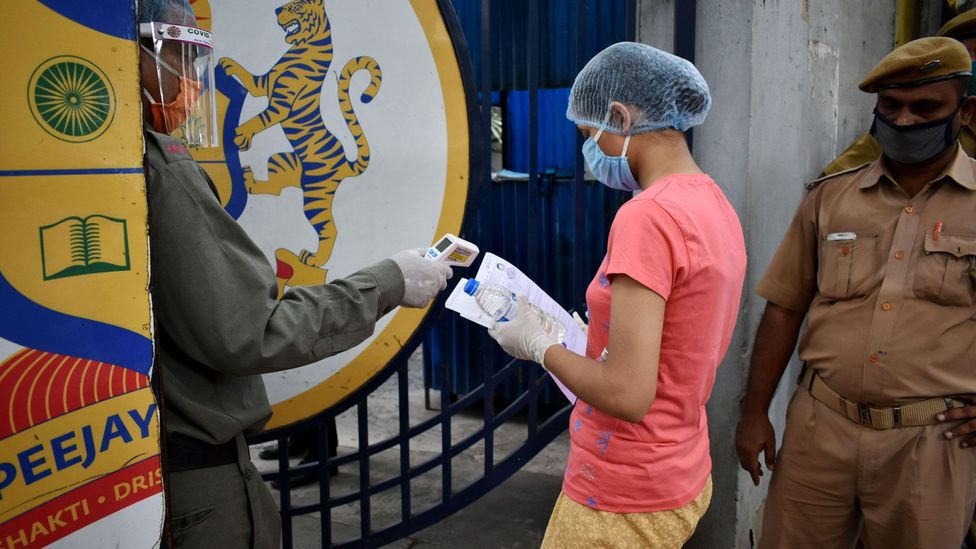 A student's temperature is taken before she enters a test centre to write the NEET in Kolkata (Credit: Alamy)