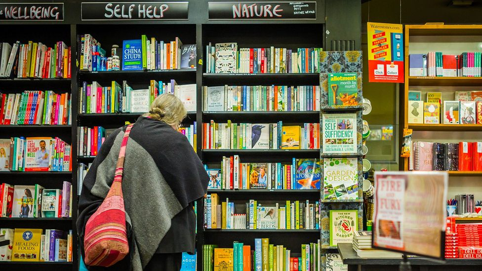 Entire sections of book shop shelving are often dedicated to self-help books that promise to make us happier (Credit: Gerry Walden/Alamy)