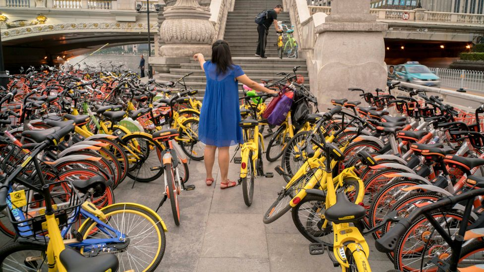 A multitude of choice of bike shares in large Chinese cities led to a surplus of bikes, many of which ended up abandoned, vandalised or confiscated (Credit: Getty Images)