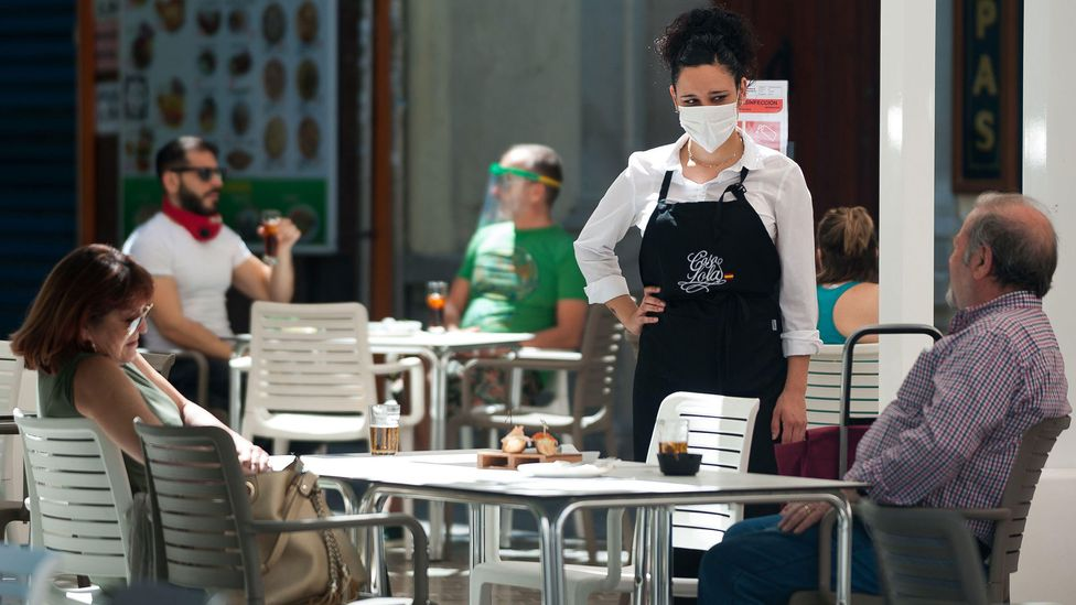 Ever had a job that required you to smile? Masks enable some people, such as restaurant servers, to drop their forced grins and do their work with less burden (Credit: Alamy)