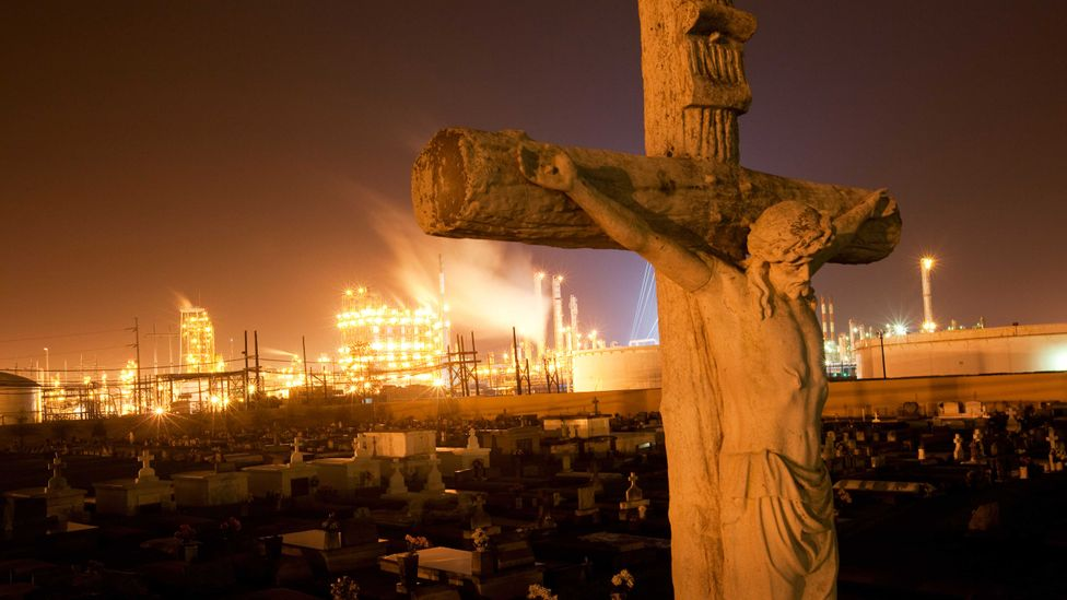 A graveyard in Louisiana with a chemical plant on the horizon (Credit: Alamy)
