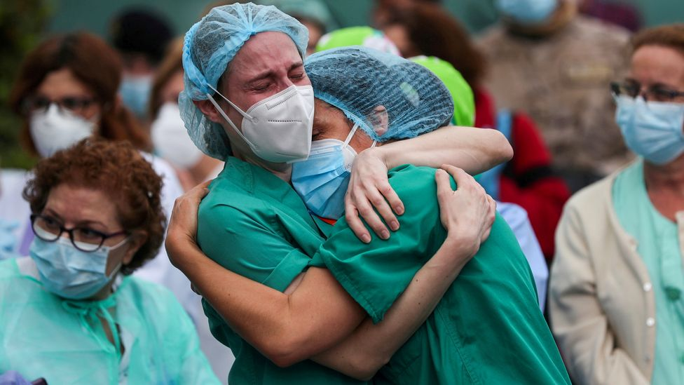 Health workers embrace following the death of a colleague in Spain (Credit: Susana Vera/Reuters)