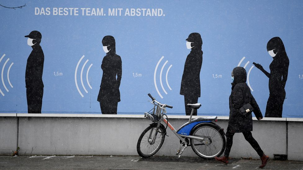 "A woman walks next to a poster in Germany reading ""The best team. With distance"" (Credit: Andreas Gebert/Reuters)"