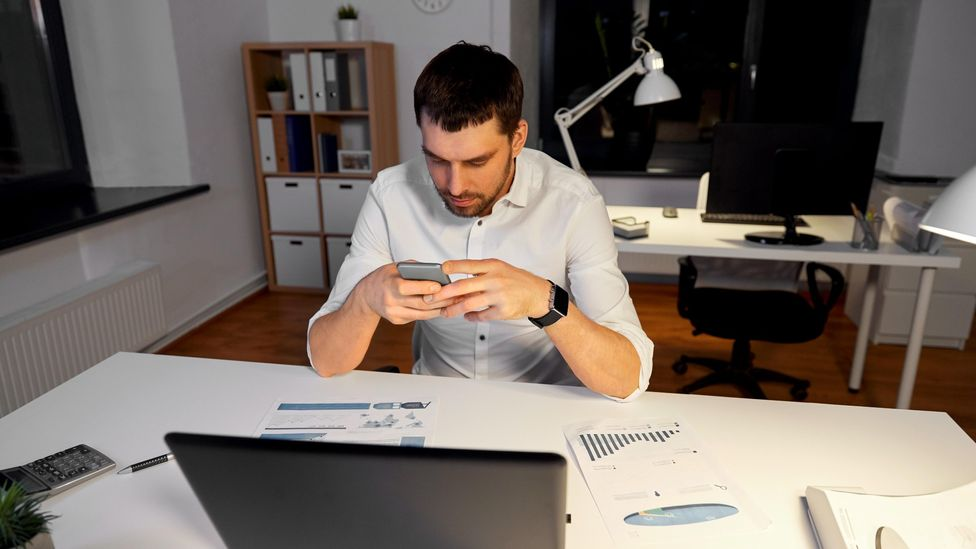 File image of a man looking at his phone in front of his laptop