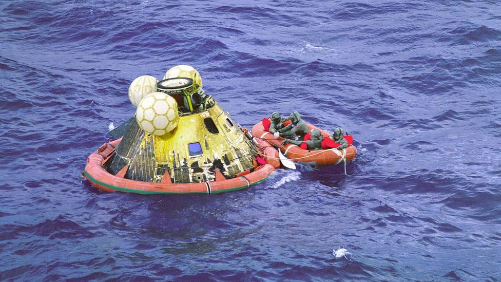 The three astronauts plus a diver wait to be picked up, after opening the capsule (Credit: Nasa)