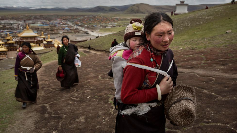 A Tibetan woman carrying a baby on her back (Credit: Getty Images)