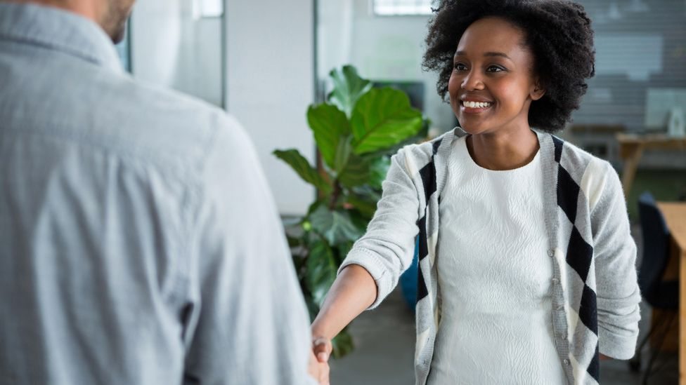 Young woman shaking hands with a colleague