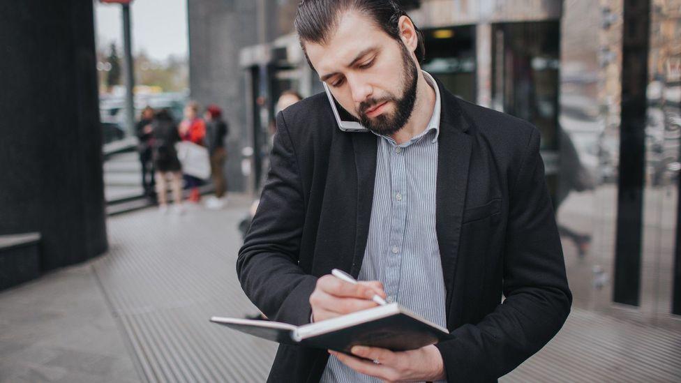Man on phone writing notes while walking
