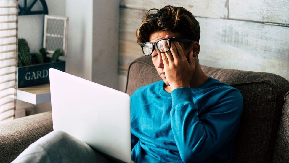 Tired woman staring at laptop