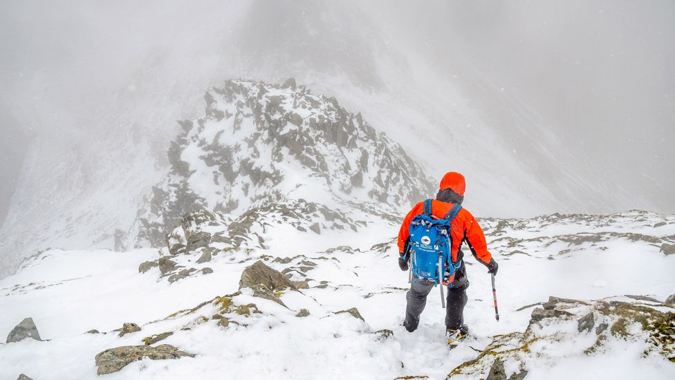 Fell Top Assessor hiking down Helvellyn mountain, Lake District, in the snow