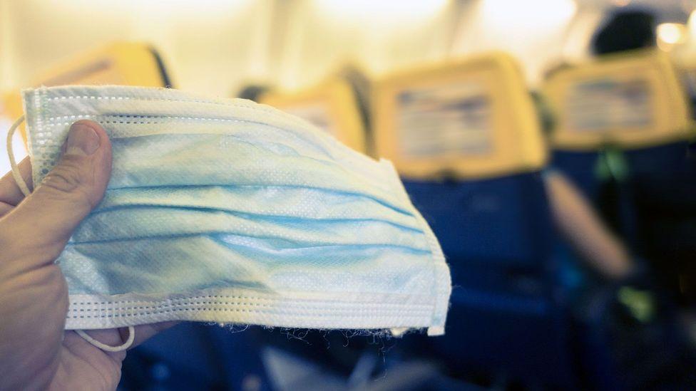 Plane passenger holding a mask