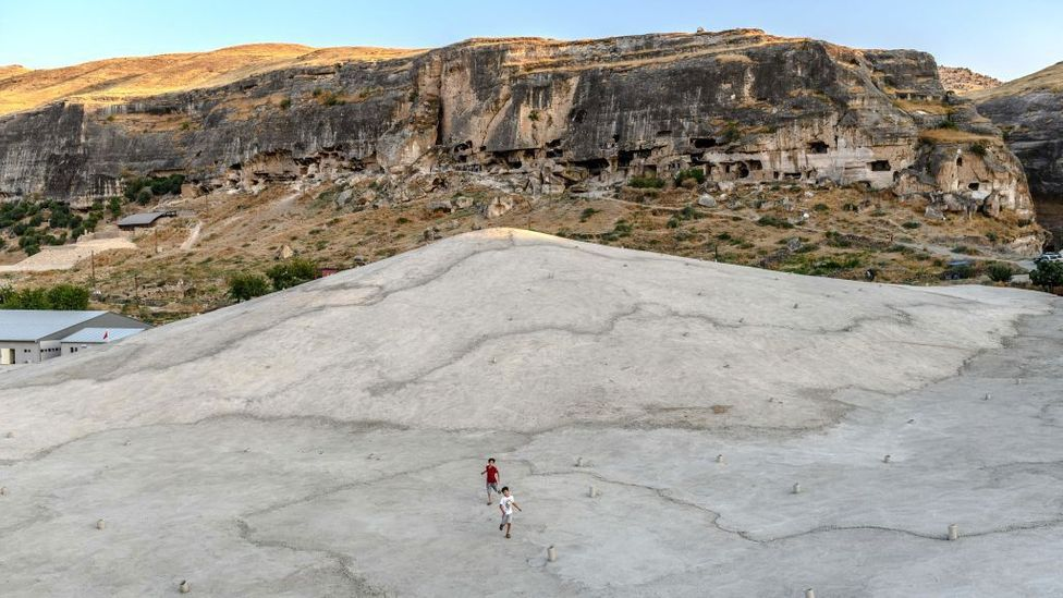 Children play on a concrete plain created to protect a mosque in Hasankeyf, Turkey from the deliberate flooding of a reservoir (Credit: Bulent Kilic/Getty Images)