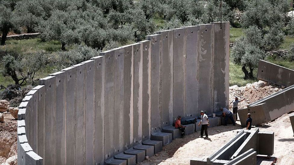 Concrete builds, but it can also divide. A controversial barrier in the town of Beit Jala in the West Bank (Credit: Thomas Coex/Getty Images)