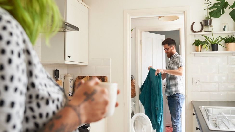 Woman in the kitchen drinking coffee as man does the laundry
