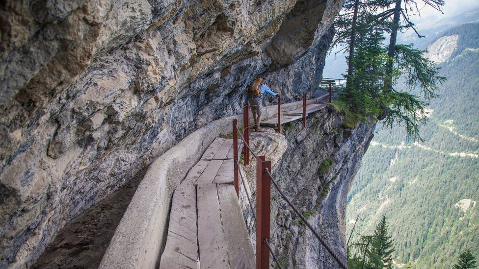 A hiker on the Bisse du Rho trail, Switzerland