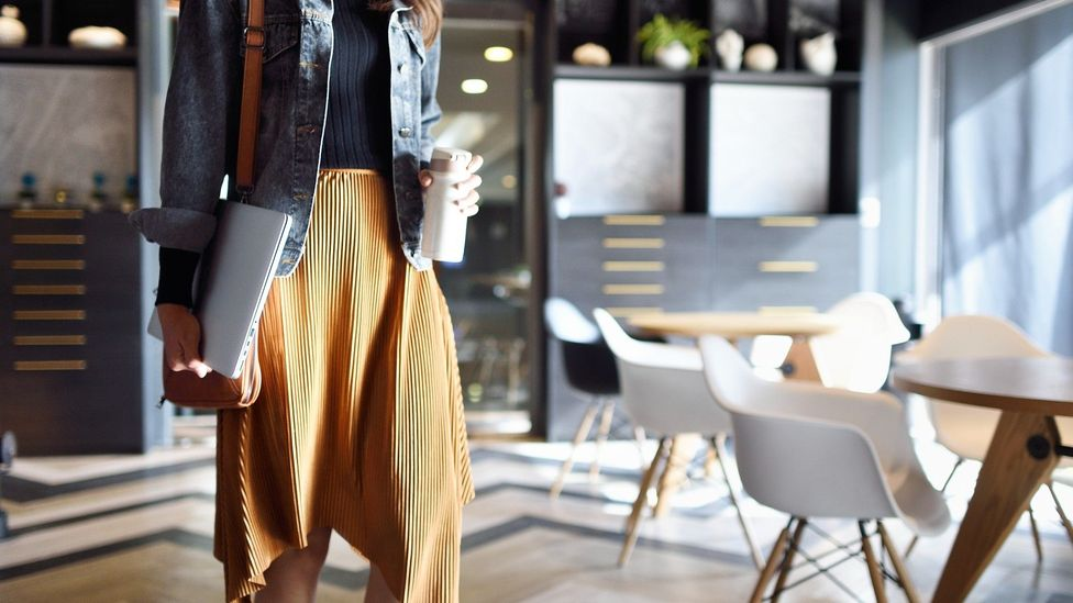 Woman carrying coffee and laptop heading to work
