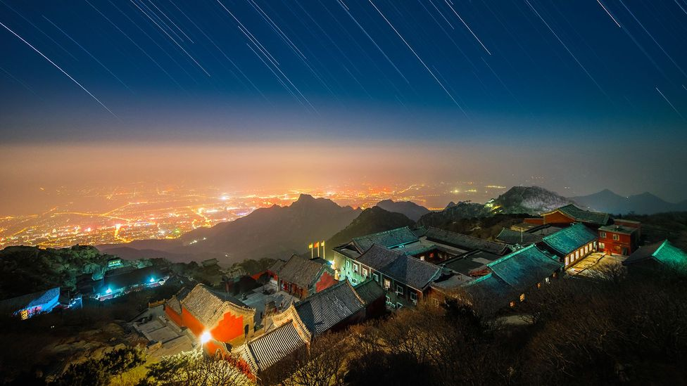 The glow given off by large towns and cities at night can often be seen for many miles around (Credit: Dneutral Han/Getty Images)