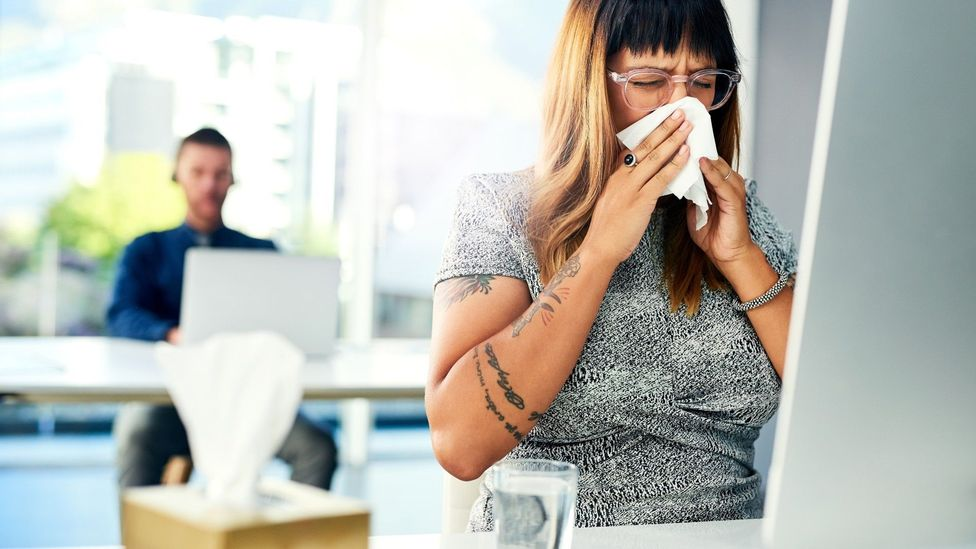 Worker blowing her nose at her desk