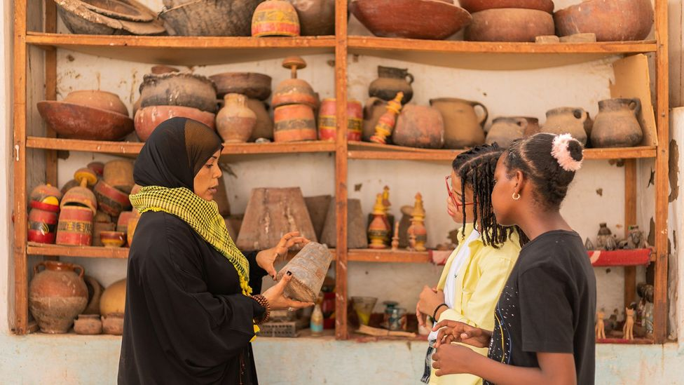 Amberkab uses a traditional copper weight to explain the traditional barter economy to Tarek and Merghany (Credit: Mai Farouk)