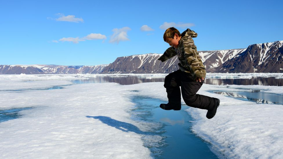 A young Inuit boy jumping over a crack on an ice floe, Nanavut (Credit: Alamy)