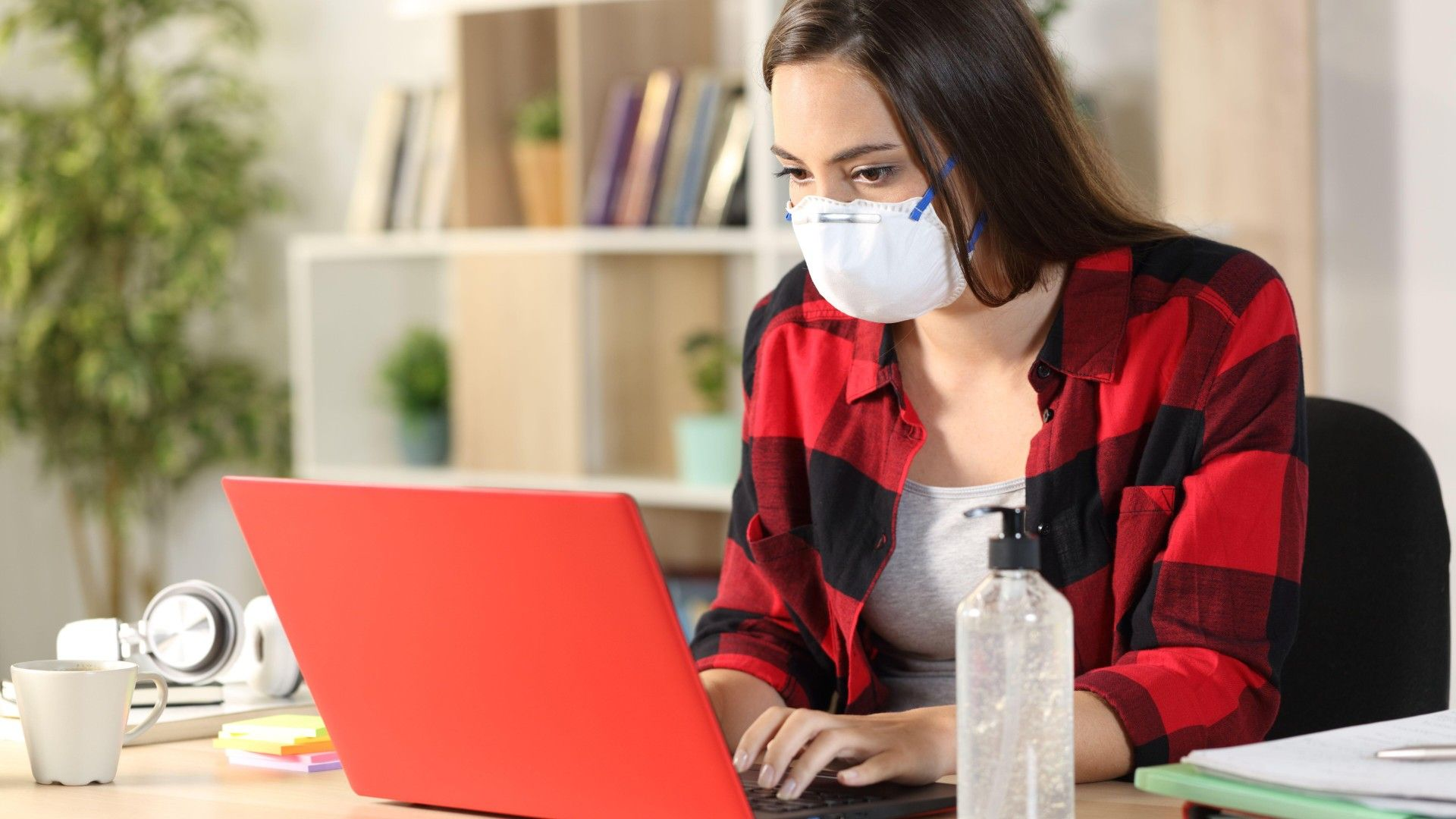 Stock image of a masked woman typing on a laptop