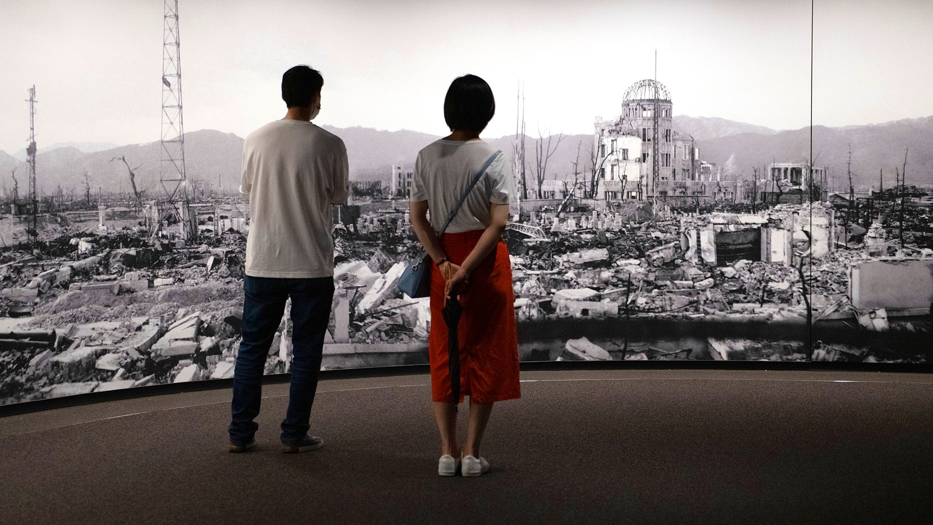 Two museum visitors look at image of destruction, Hiroshima (Credit: Getty Images)